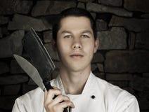 Verlicht portret van aardige en aantrekkelijke mensenchef-kok in eenvormig op de achtergrond van de steenmuur Mensenchef-kok het  Royalty-vrije Stock Foto's