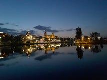 Verlichte brug over een kalme rivier in recente avond stock fotografie