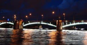 Verlichte brug overdwars van rivier Neva op de achtergrond van de nachthemel Stock Foto