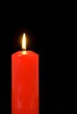Verlichte rode kaars op zwarte Royalty-vrije Stock Afbeeldingen