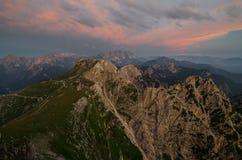 Verlichte roodachtige wolken over Mangart-Pas en weg, Julian Alps, het nationale park van Triglav, Slovenië, Europa stock afbeeldingen