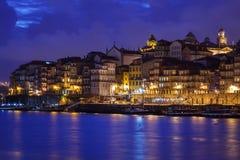 Verlichte stadsgebouwen en boten die op kleurrijke lichten wijzen in Rivier Douro langs waterkant in Porto, Portugal Royalty-vrije Stock Afbeeldingen