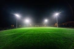 Verlichte voetbalspeelplaats met groen gras stock afbeelding
