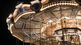 Verlichte vrolijk gaat rond in park Helder het verlichte rotonde spinnen in prachtig pretpark bij nacht stock videobeelden