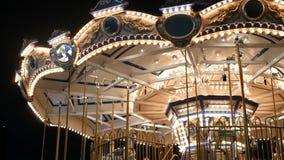 Verlichte vrolijk gaat rond in park Helder het verlichte rotonde spinnen in prachtig pretpark bij nacht stock footage