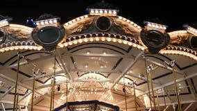Verlichte vrolijk gaat rond in park Helder het verlichte rotonde spinnen in prachtig pretpark bij nacht stock video