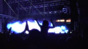 Verlichting die op stadium, silhouetten opvlammen van publiek die rots van overleg genieten stock videobeelden