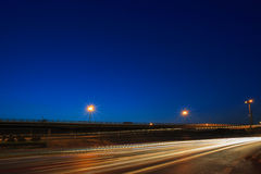 Verlichting van voertuig het drijven op asfaltweg tegen mooie bl stock fotografie