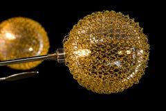 Verlichtingsballen op de gouden kroonluchter in de lamplicht, Lampen op de donkere achtergrond Close-up Royalty-vrije Stock Afbeeldingen
