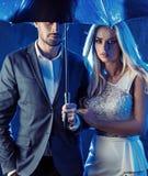 Verliebte Paare, die auf einem regnerischen bacground aufwerfen lizenzfreie stockbilder