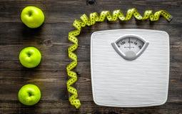 Verlieren Sie Gewichtkonzept Badezimmerwaage, messendes Band, Äpfel auf Draufsicht des hölzernen Hintergrundes lizenzfreie stockfotografie