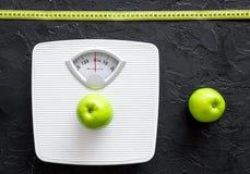 Verlieren Sie Gewichtkonzept Badezimmerwaage, messendes Band, Äpfel auf Draufsicht des schwarzen Hintergrundes Lizenzfreie Stockfotografie