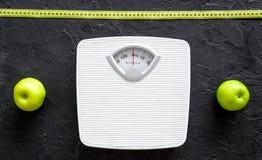 Verlieren Sie Gewichtkonzept Badezimmerwaage, messendes Band, Äpfel auf Draufsicht des schwarzen Hintergrundes Lizenzfreies Stockbild