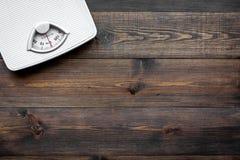 Verlieren Sie Gewichtkonzept Skala auf dunklem hölzernem copyspace Draufsicht des Hintergrundes Stockfotos