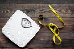 Verlieren Sie Gewichtkonzept Skala und messendes Band auf Draufsicht des dunklen hölzernen Hintergrundes lizenzfreies stockfoto