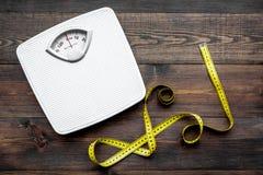 Verlieren Sie Gewichtkonzept Skala und messendes Band auf Draufsicht des dunklen hölzernen Hintergrundes lizenzfreie stockfotos