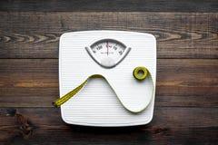 Verlieren Sie Gewichtkonzept Skala und messendes Band auf Draufsicht des dunklen hölzernen Hintergrundes lizenzfreie stockfotografie