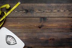 Verlieren Sie Gewichtkonzept Skala und messendes Band auf dunklem hölzernem Draufsicht-Kopienraum des Hintergrundes lizenzfreies stockbild