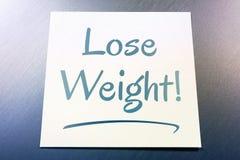 Verlieren Sie Gewichts-Anzeige auf dem Papier, das auf gebürstetem Aluminium des Kühlschranks liegt Stockbilder