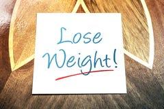 Verlieren Sie Gewichts-Anzeige auf dem Papier, das auf Holztisch liegt Stockbild