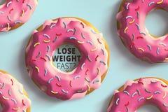Verlieren Sie schnellen Text des Gewichts im Donut auf einem blauen Hintergrund Lizenzfreies Stockbild