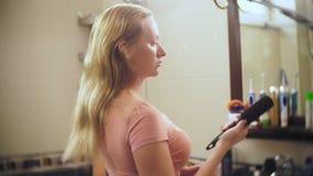 Verlierendes Haar der Frau, eine blonde Frau mit dem langen Haar wird im Badezimmer vor dem Spiegel gekämmt Haar bleibt auf stock video