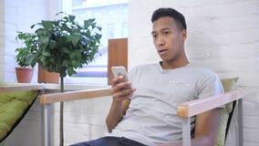 Verlies, Afrikaanse Ontwerper Watching Failure op Smartphone stock video