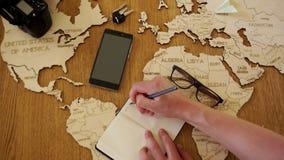verliezen-op de mens schrijft in zijn notitieboekje het plan van zijn reizen Reisbureau, reisorganisatie Vakantie, de zomervakant stock footage