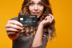 Verliezen-op portret die van de gelukkige jonge donkerbruine creditcard van de vrouwenholding en kleurrijke het winkelen zakken,  royalty-vrije stock foto's