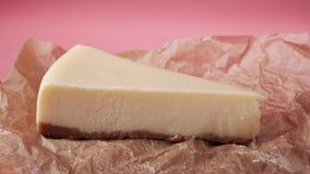 Verliezen-op van plak van verse traditionele kaastaart op een voedsel verpakkingsdocument Kader Geïsoleerdo op roze stock video