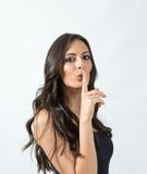 Verlockende attraktive gebräunte Schönheitsfrau mit dem Finger über ihrer Mundstillegeste Stockfotos