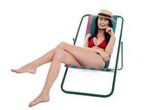 Verlockende Bikinifrau, die auf einem deckchair sich entspannt Stockfoto