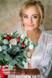Verlockende blonde Braut mit rotem und grünem Blumenstrauß in ihren Händen Stockfotografie