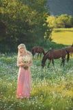 Verlockende blonde Damenfrau der blauen Augen im luftigen Kleid des kleinen Fingers auf der Wiese der Gänseblümchenkamille Blumen Stockbild