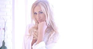 Verlockende blonde Frau in der weißen schauenden Kamera Lizenzfreie Stockfotografie