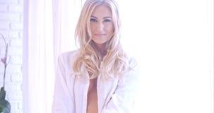 Verlockende blonde Frau in der weißen schauenden Kamera Lizenzfreie Stockbilder