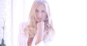Verlockende blonde Frau in der weißen schauenden Kamera Lizenzfreie Stockfotos
