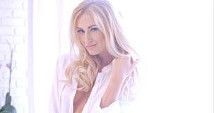 Verlockende blonde Frau in der weißen schauenden Kamera Stockfoto