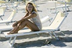 Verlockende blonde Frau, die auf einem Klappstuhl sitzt Stockfotografie