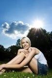 Verlockende blonde Frau, die auf einer Rasenfläche sitzt Stockbilder