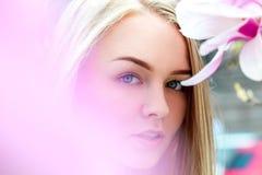 Verlockende blonde Frau mit blauen Augen in blühenden rosa Blumen Stockfotografie