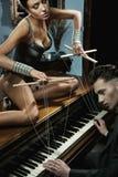 Verlockende Frau auf dem Klavier Stockfotos