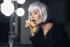 Verlockende Frau, die Pizza isst und Champagner in der Umkleidekabine trinkt Stockbild