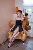 Verlockende Frau im schwarzen Kleid sitzen Lizenzfreie Stockbilder