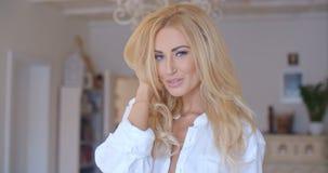 Verlockende Frau im weißen Hemd, das Kamera betrachtet Stockfotografie