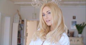 Verlockende Frau im weißen Hemd, das Kamera betrachtet Stockbilder