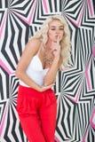 Verlockende junge blonde Frau, die an Druckwand aufwirft Lizenzfreies Stockbild