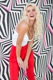 Verlockende junge blonde Frau, die an Druckwand aufwirft Lizenzfreie Stockbilder