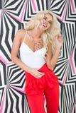 Verlockende junge blonde Frau, die an Druckwand aufwirft Stockfotos