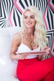 Verlockende junge blonde Frau mit einer Tablette Stockbild